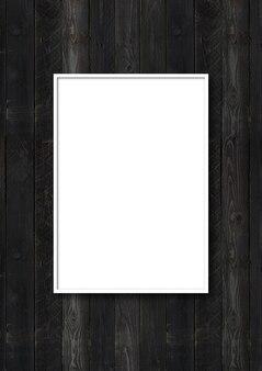 Porta-retrato branco pendurado em uma parede de madeira preta