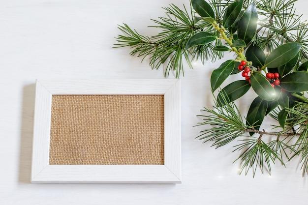 Porta-retrato de madeira branca com tecido de serapilheira em branco, ramos de plantas verdes sobre fundo branco.
