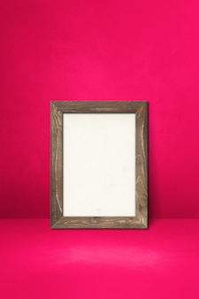 Porta-retrato de madeira encostado em uma parede rosa. modelo de maquete em branco