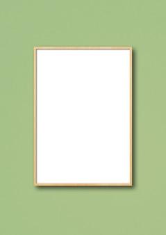 Porta-retrato de madeira pendurada em uma parede verde clara.