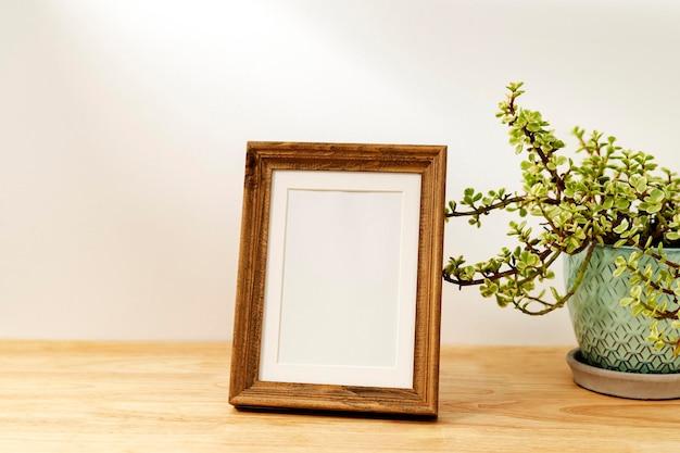 Porta-retrato decorativo em branco na mesa de madeira