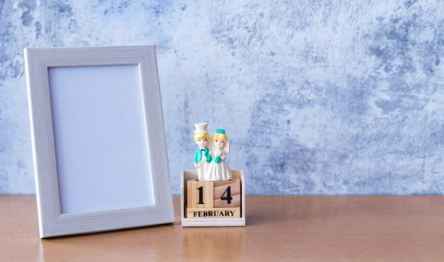 Porta-retrato e casal de noivos em miniatura na mesa. dia dos namorados