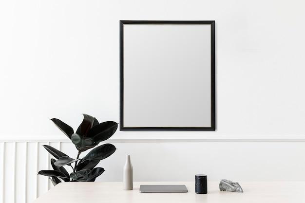 Porta-retrato em branco pendurado em uma parede branca