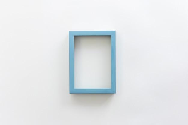 Porta-retrato em branco vazio de borda azul contra o pano de fundo branco