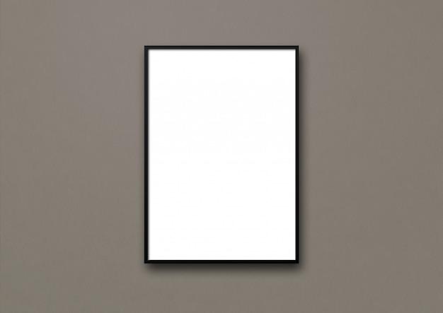 Porta-retrato preto pendurado em uma parede cinza escuro. template em branco
