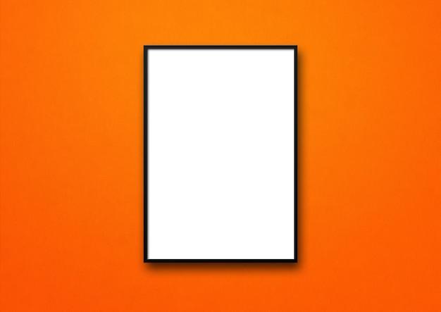 Porta-retrato preto pendurado em uma parede laranja.