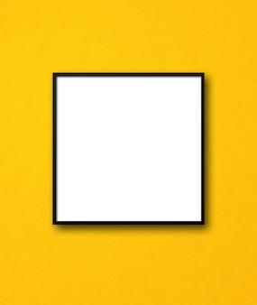 Porta-retrato quadrado preto pendurado em uma parede amarela. modelo de maquete em branco
