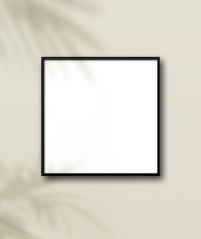 Porta-retrato quadrado preto pendurado em uma parede bege claro.