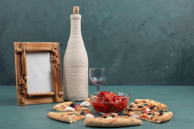 Porta-retrato, uma garrafa, tigela de pimenta vermelha em conserva, fatias de pizza na mesa azul.