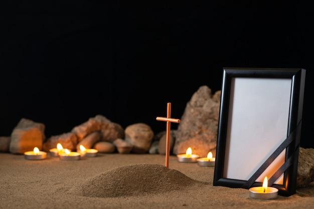 Porta-retrato vazio com velas de pedras e uma pequena sepultura na superfície escura