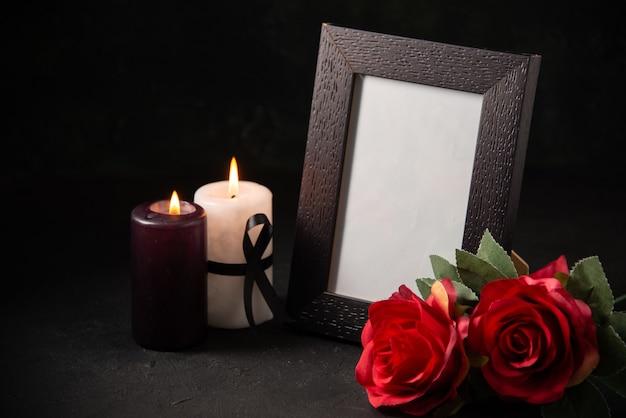 Porta-retratos de vista frontal com flores vermelhas e velas em uma superfície escura