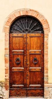 Porta velha de madeira marrom no centro de san gimignano.
