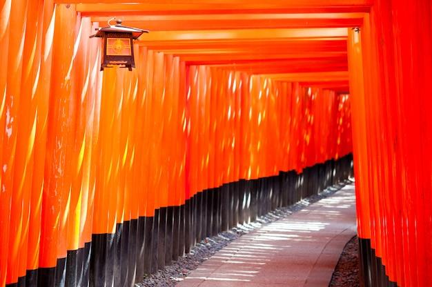 Porta vermelha chamada torii e lanterna pendurada no santuário de fushimi inari, japão