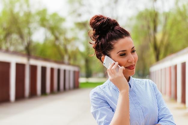 Portait de jovem falando ao telefone ao ar livre