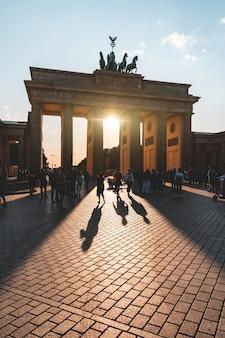 Portão de berlim, brandemburgo com turista em silhueta ao pôr do sol