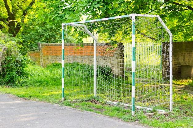 Portão de bola em um campo de futebol no parque cercado por árvores verdes