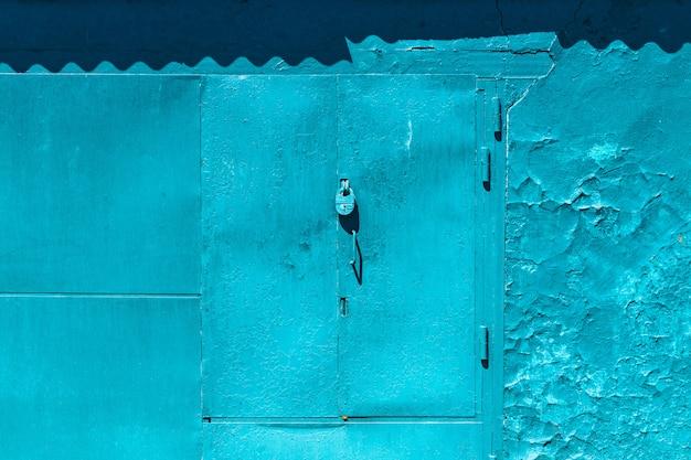 Portão de garagem azul imperfeito fechado com close-up de cadeado