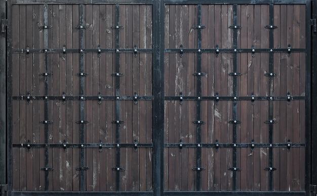 Portão de madeira marrom com listras de metal forjadas. planos de fundo e texturas