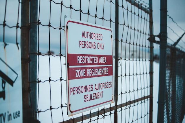 Portão de metal preto com sinal de aviso