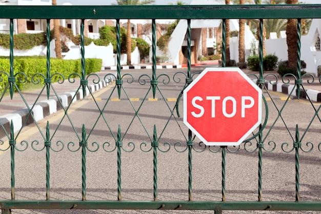 Portão fechado com um sinal vermelho na entrada do hotel