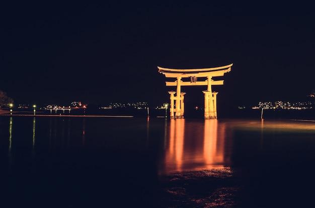 Portão flutuante torii iluminado de itsukushima à noite, miyajimacho, japão
