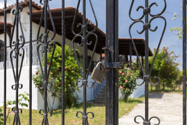 Portão para uma pousada na grécia fechada por uma fechadura devido às restrições da pandemia covid-19