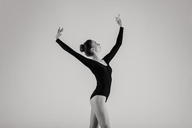 Portarit de sensual dançarina de callet caucasiana profissional em traje corporal e sapatos pointes posando no chão em branco.