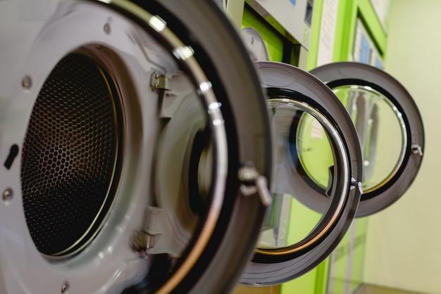 Portas abertas de máquinas de lavar industriais em uma lavanderia pública, cadeado de fechadura