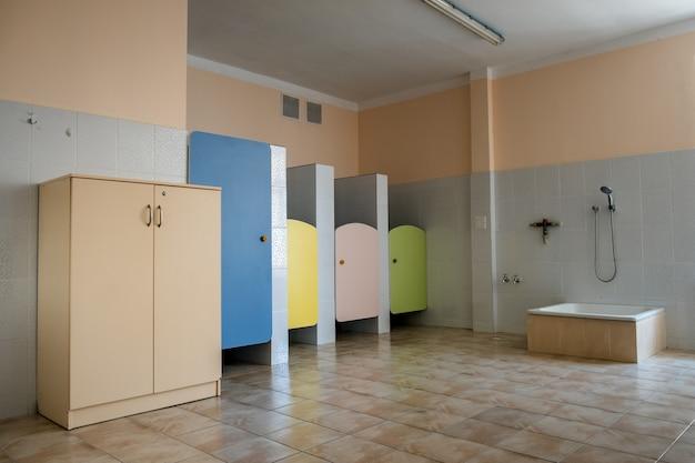Portas coloridas do banheiro no interior do banheiro da escola primária.