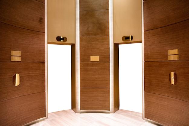 Portas de elevador brancas em branco na sala de madeira com decoração de material dourado