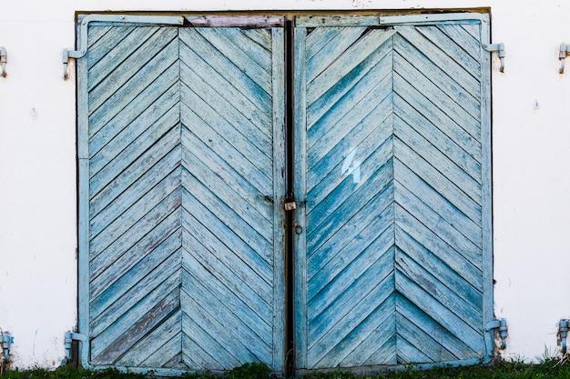 Portas de garagem velhas, azuis e enviesadas em uma parede de tijolos em colapso