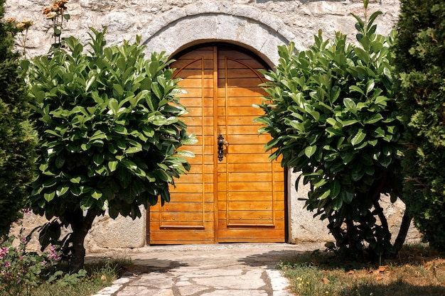 Portas de madeira de uma casa de pedra rodeada por arbustos de louro.