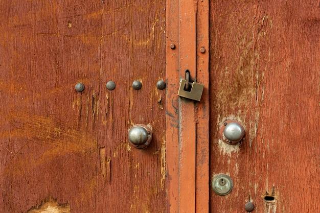 Portas de madeira envelhecida com rebites e fechadura de metal