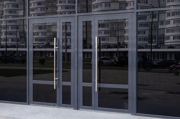 Portas de vidro preto refletindo o bloco de apartamentos do lado oposto