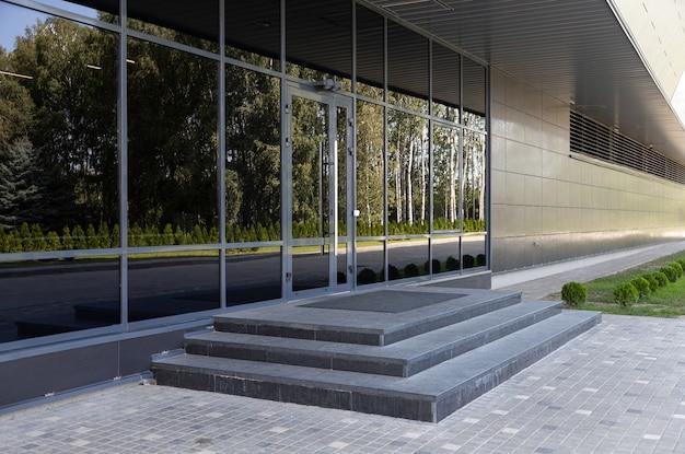 Portas de vidro refletindo arbustos e árvores verdes no lado oposto e degraus de pedra