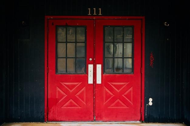 Portas duplas vermelhas para o prédio 111 com painéis pretos
