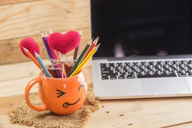 Portátil com a caneca feliz da cara do enrugamento do smiley para o conceito digital do artista da ideia.