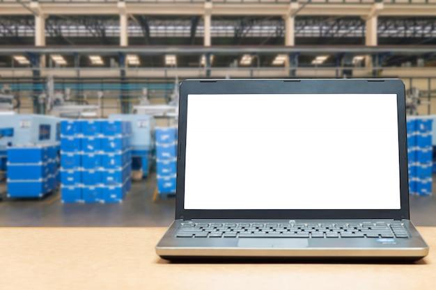 Portátil com a tela vazia na tabela com carga do armazém do borrão na fábrica. conceito de fábrica inteligente.
