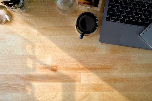 Portátil com o copo de café marrom e espaço da cópia na tabela de madeira da mesa. área de trabalho