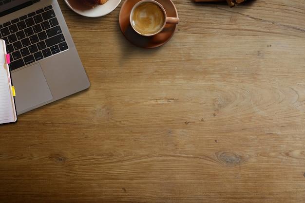 Portátil com o copo de café marrom e espaço da cópia na tabela de madeira da mesa.