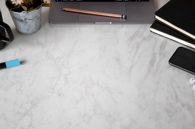 Portátil da mesa do mármore do escritório, livros, caneca de café e flor.