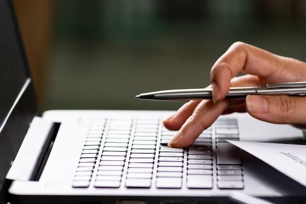 Portátil da tecla da imprensa da mão da mulher de negócios na mesa de escritório com original da indicação do documento das estatísticas.