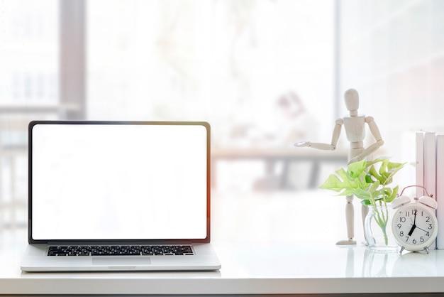 Portátil da tela vazia do modelo na tabela de madeira branca no espaço detrabalho.