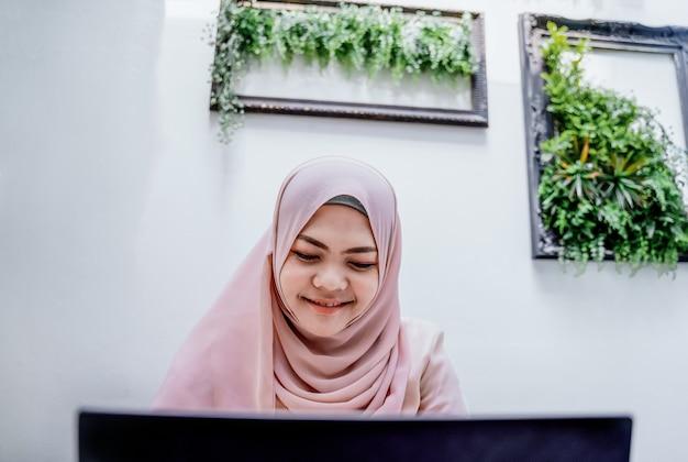Portátil de datilografia da mulher muçulmana nova segura. mulher árabe de sorriso que senta-se na sala branca.