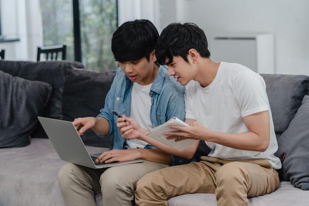 Portátil de trabalho dos pares alegres asiáticos novos na casa moderna. os homens da ásia lgbtq + felizes relaxam divertidos usando o computador e analisando suas finanças na internet juntos enquanto estão deitados no sofá na sala de estar em casa.