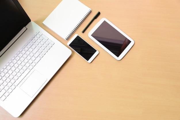 Portátil do caderno do computador com tabuleta digital e smartphone branco na mesa de madeira. na sala de negócios