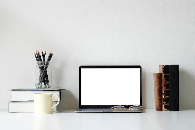 Portátil do modelo do espaço de trabalho do escritório, livros, lápis e caneca de café na mesa de escritório.