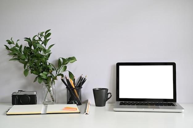 Portátil e câmera do computador do espaço de trabalho com papel do caderno com café.