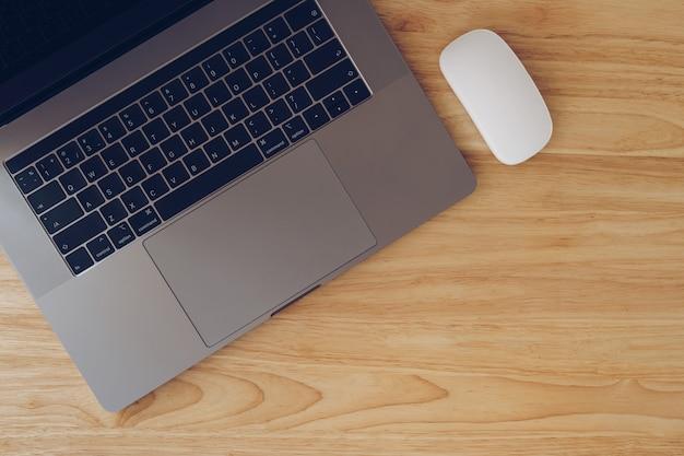 Portátil e rato na opinião de tampo da mesa de madeira com espaço da cópia.