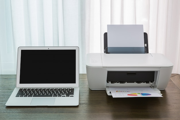 Portátil em uma mesa de madeira com uma impressora